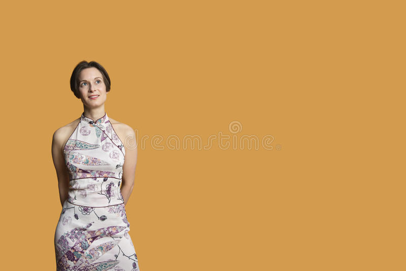Mulher adulta meados de feliz que está sobre o fundo colorido foto de stock