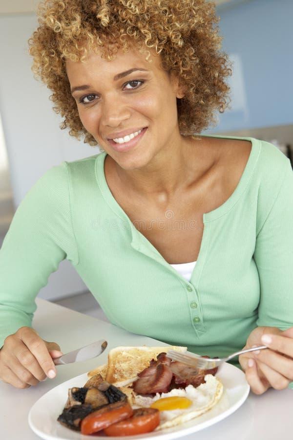 Mulher adulta meados de que come o pequeno almoço fritado insalubre imagens de stock royalty free