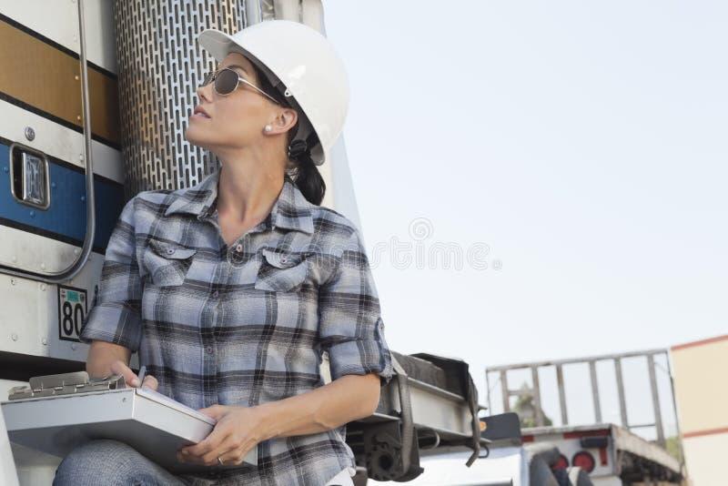 Mulher adulta meados de que inspeciona o caminhão da madeira fotografia de stock royalty free