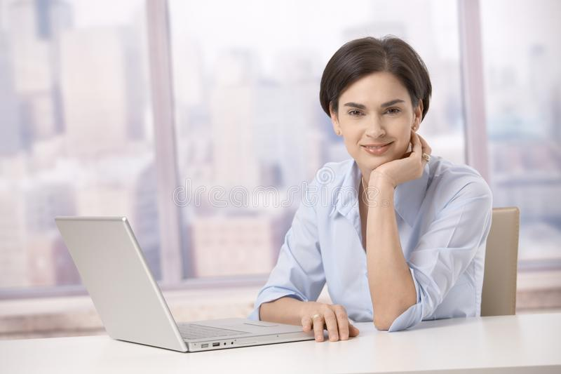 Mulher adulta meados de que sorri com computador imagem de stock