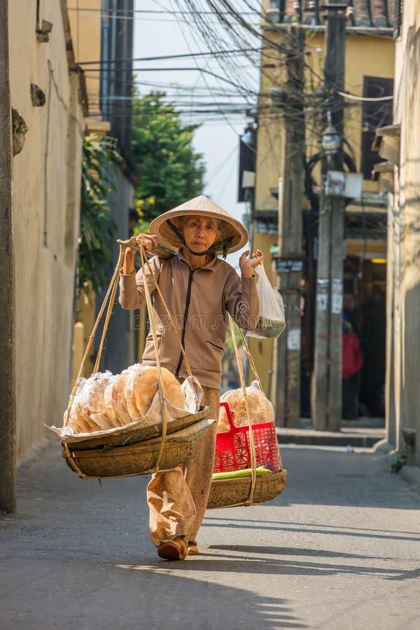 Mulher adulta não identificada na roupa vietnamiana tradicional que leva buskets com pão foto de stock royalty free
