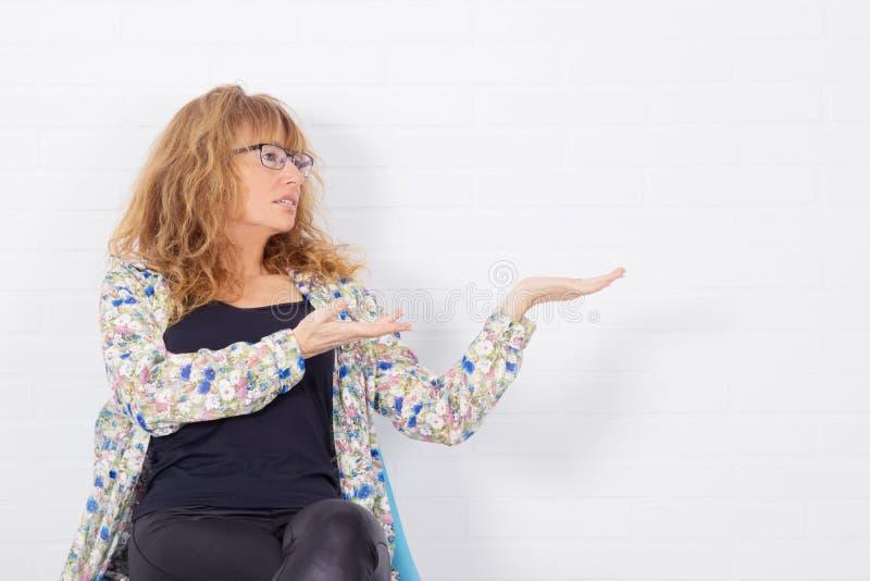 Mulher adulta na cadeira fotografia de stock