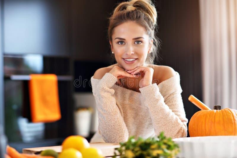 Mulher adulta na cozinha que prepara pratos da abóbora para Dia das Bruxas fotografia de stock