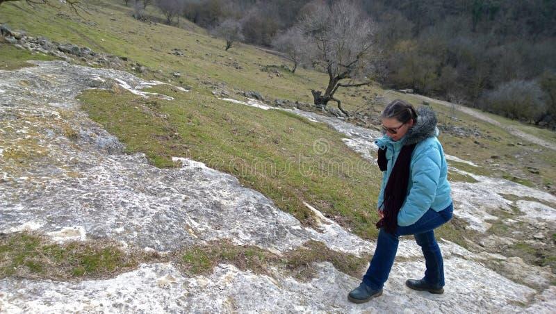 Mulher adulta nas calças de brim e em um revestimento durante uma caminhada nas montanhas Mal elevações em uma estrada difícil foto de stock