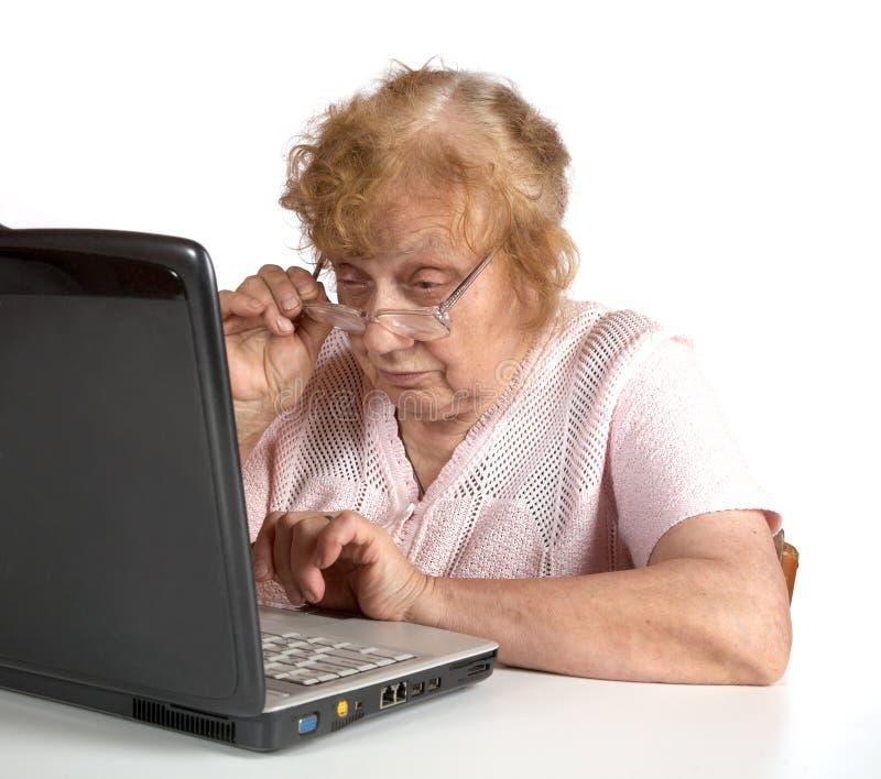 A mulher adulta nos vidros olha o caderno imagem de stock