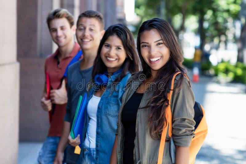 Mulher adulta nova latino-americano com grupo de estudantes na linha imagem de stock royalty free