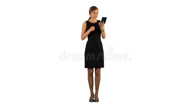 Mulher adulta nova que aplica o batom ela mesma no fundo branco isolado foto de stock royalty free
