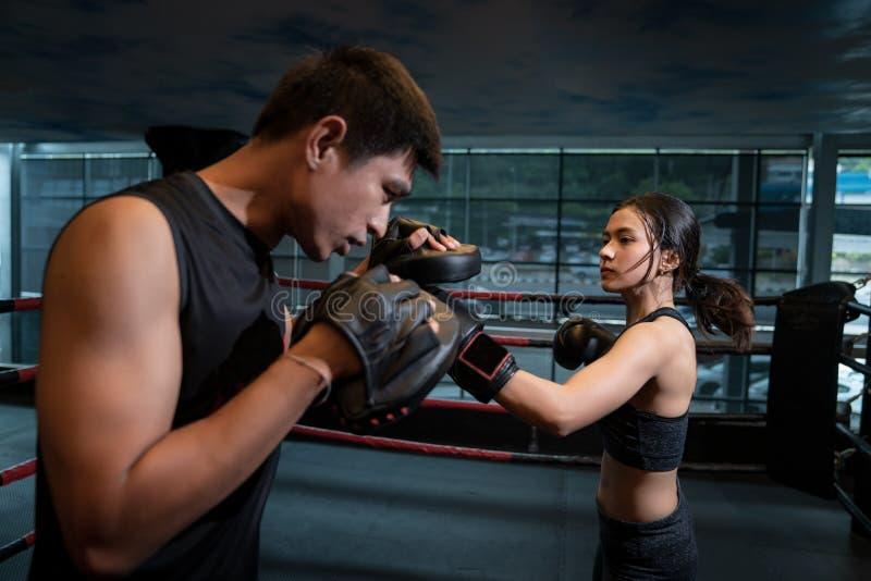 Mulher adulta nova que faz o treinamento kickboxing com seu treinador fotografia de stock royalty free