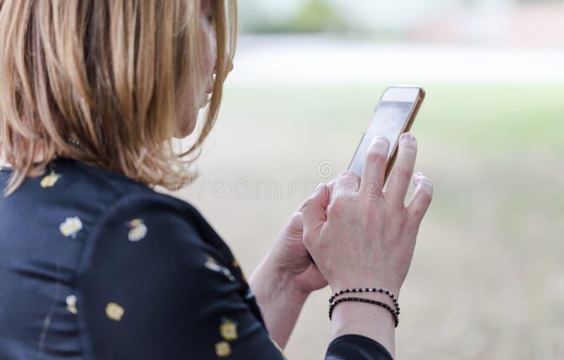 Mulher adulta nova que usa o telefone da câmera como um espelho fotografia de stock