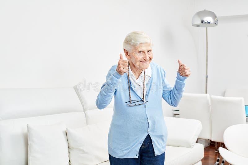 A mulher adulta otimista mantém seus polegares acima fotografia de stock
