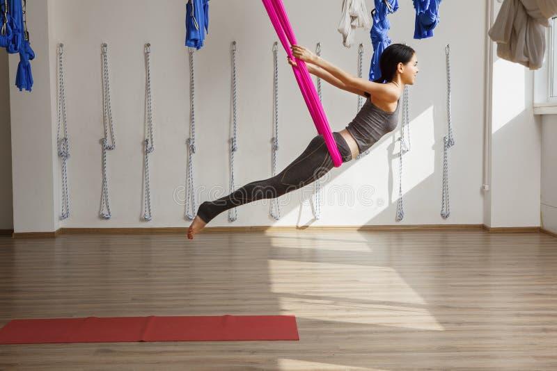 A mulher adulta pratica a posição da ioga da inversão no gym foto de stock