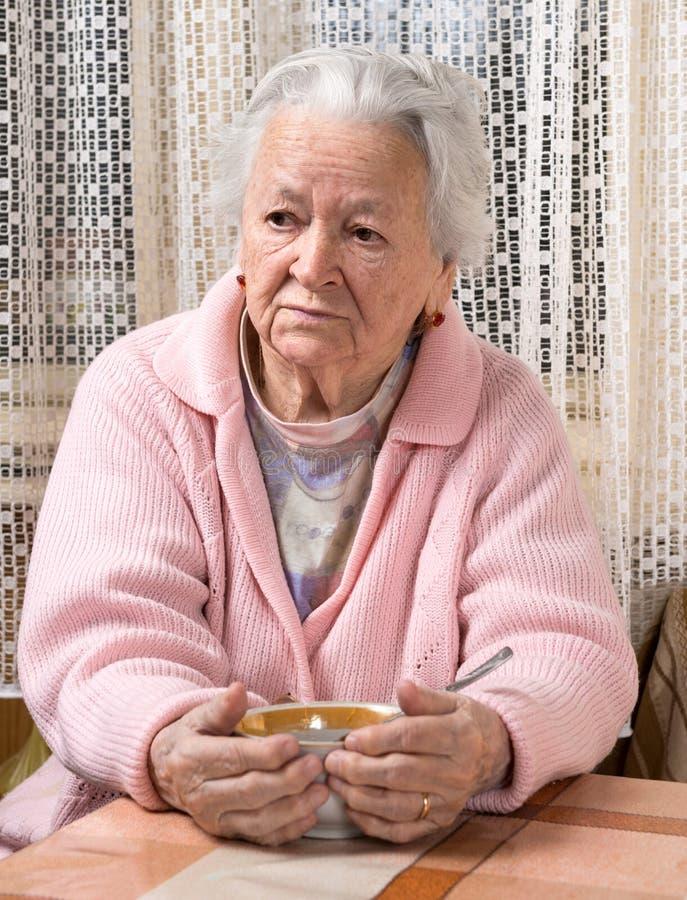 Mulher adulta que come em casa imagem de stock royalty free