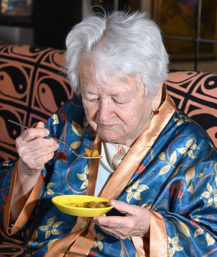 Mulher adulta que come em casa fotos de stock royalty free