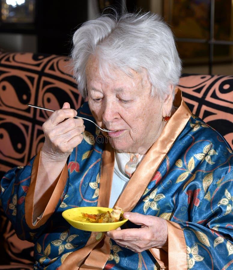 Mulher adulta que come em casa fotografia de stock