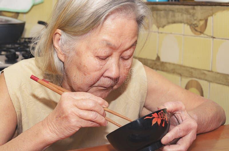 Mulher adulta que come em uma bacia foto de stock royalty free