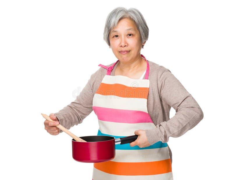 Mulher adulta que cozinha o alimento imagens de stock royalty free