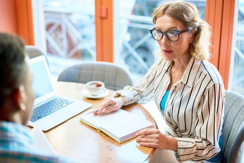 Mulher adulta que fala ao colega no café imagem de stock royalty free