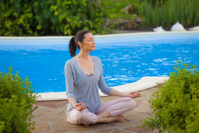 Mulher adulta que faz a ioga perto da associação imagem de stock royalty free