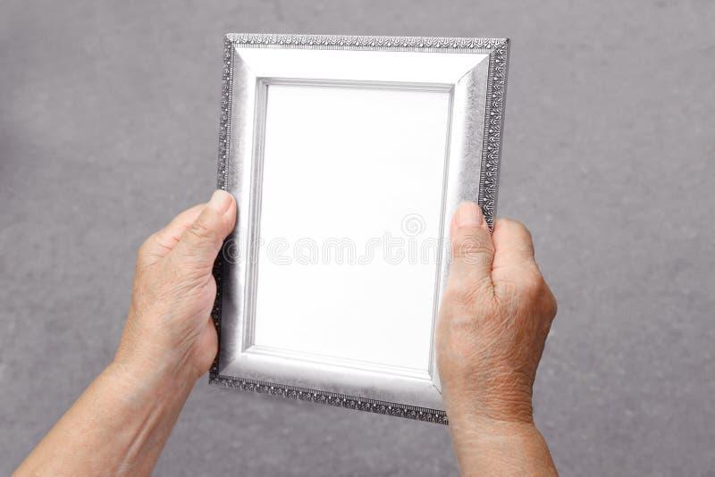 Mulher adulta que guarda o quadro da foto conceito das memórias foto de stock royalty free