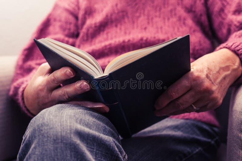 Mulher adulta que lê em casa fotografia de stock royalty free