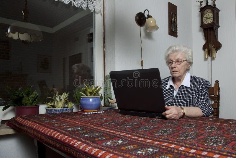 Mulher adulta que olha seu computador portátil foto de stock