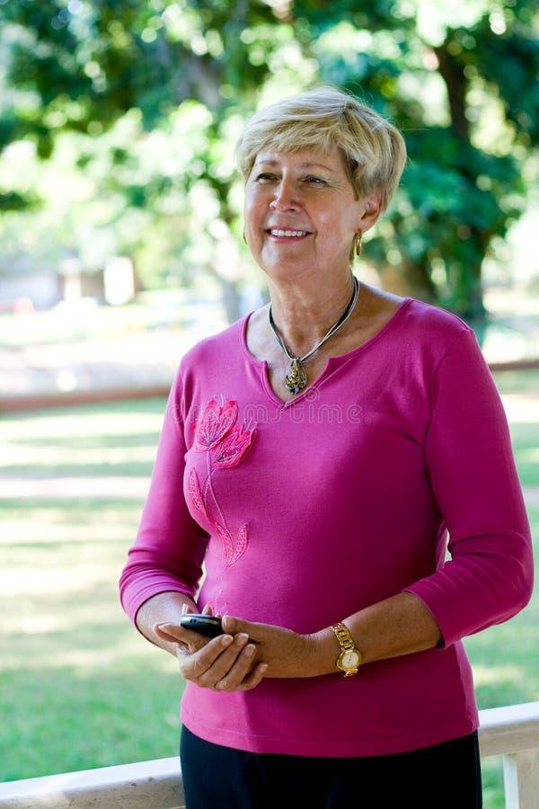 Mulher adulta que prende um telemóvel fotografia de stock