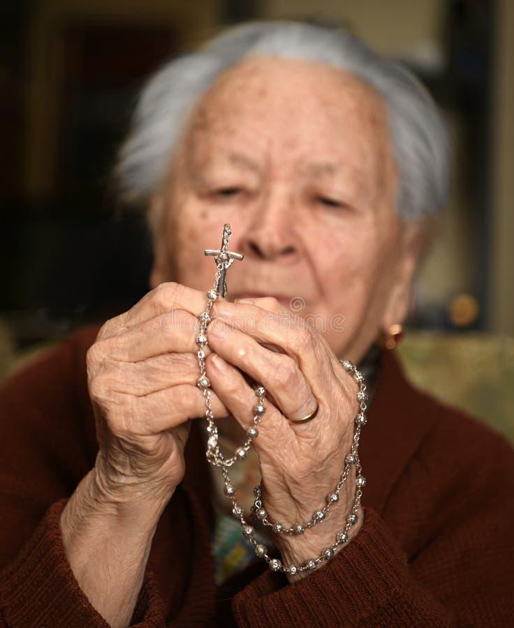 Mulher adulta que reza e que guarda o rosário de prata foto de stock royalty free