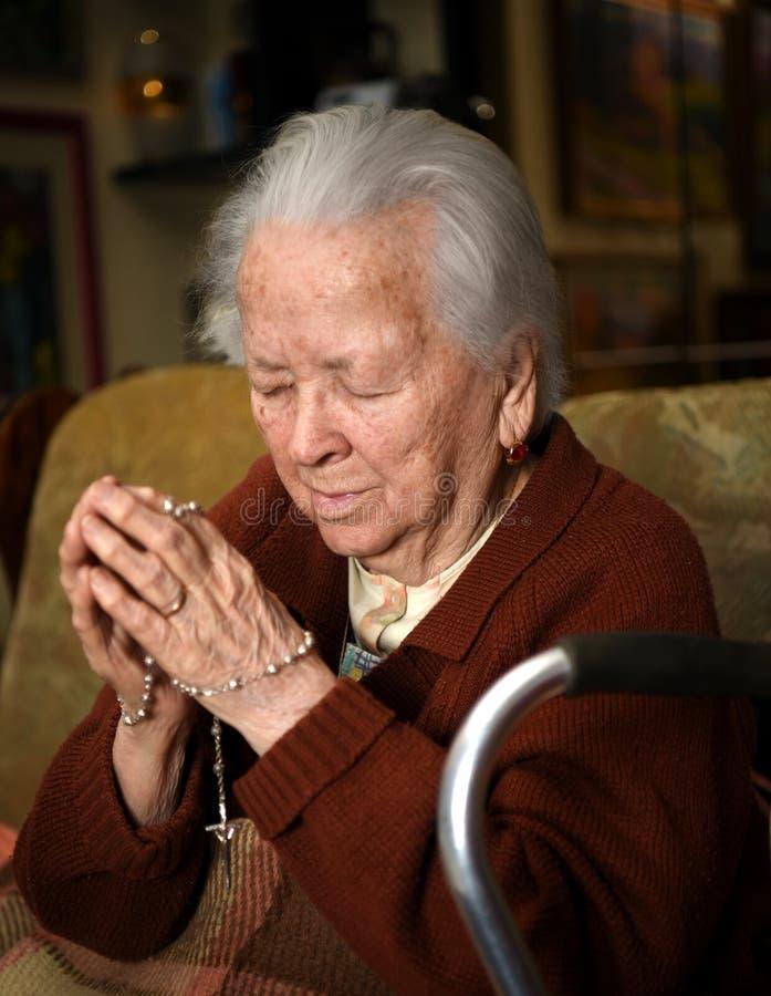 Mulher adulta que reza e que guarda o rosário de prata fotografia de stock royalty free