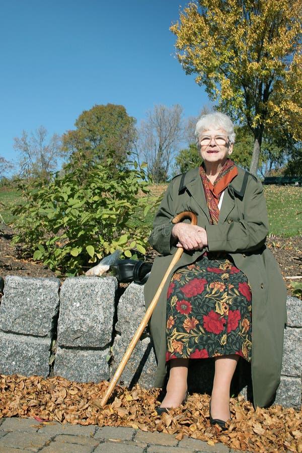 Mulher adulta que senta-se no parque foto de stock