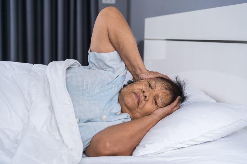 A mulher adulta que sofre da insônia está tentando dormir na cama foto de stock