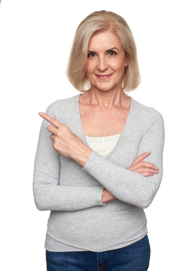 Mulher adulta que sorri e que aponta o dedo fotos de stock