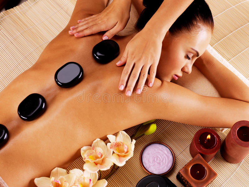 Mulher adulta que tem a massagem de pedra quente no salão de beleza dos termas imagens de stock
