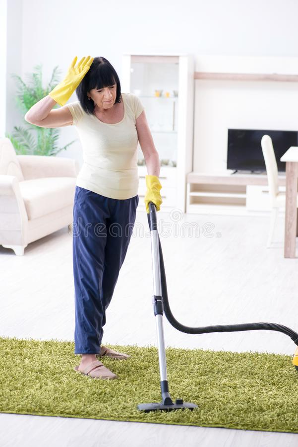 A mulher adulta superior cansado após a casa da limpeza do vácuo foto de stock royalty free