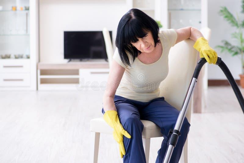 A mulher adulta superior cansado após a casa da limpeza do vácuo fotos de stock