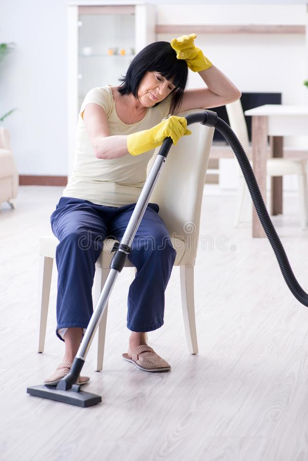A mulher adulta superior cansado após a casa da limpeza do vácuo imagens de stock royalty free