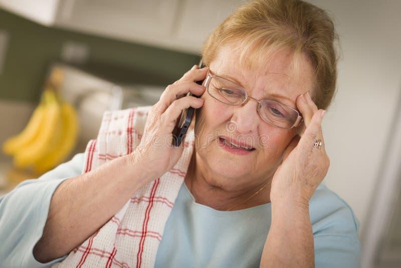 Mulher adulta superior chocada no telemóvel na cozinha imagem de stock royalty free