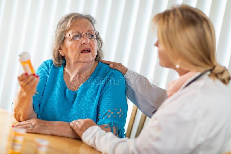 A mulher adulta superior confundida pergunta a doutor About Medicine Prescription imagem de stock