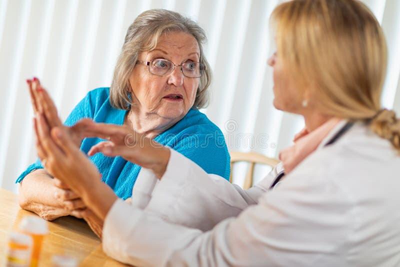 Mulher adulta superior confusa que fala com o doutor sobre a terapia da m?o imagem de stock