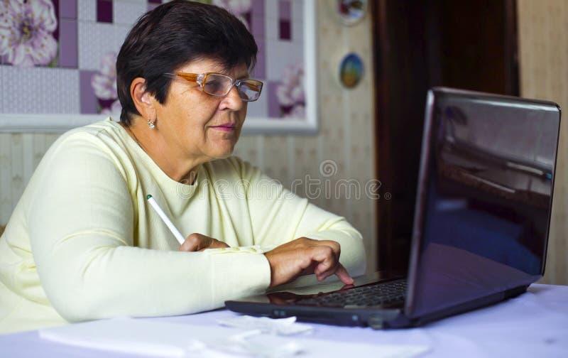 Mulher adulta superior nos monóculos que surfam o Internet no portátil em casa fotos de stock royalty free