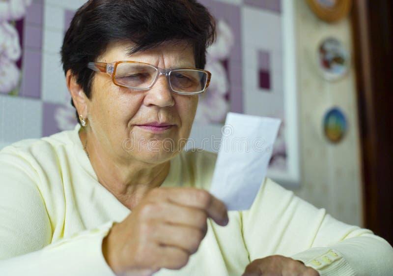 Mulher adulta superior nos monóculos que verifica custos de despesas diárias em casa fotografia de stock
