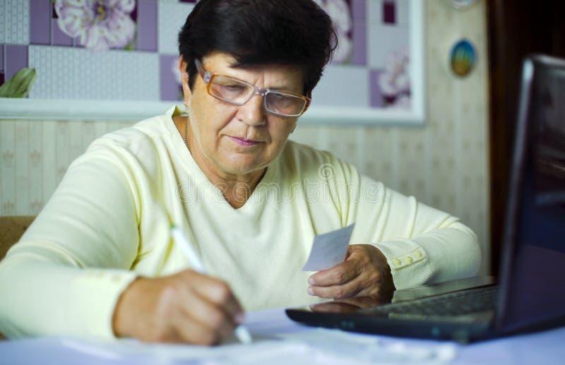 Mulher adulta superior nos monóculos que verifica custos de despesas diárias no portátil em casa fotografia de stock
