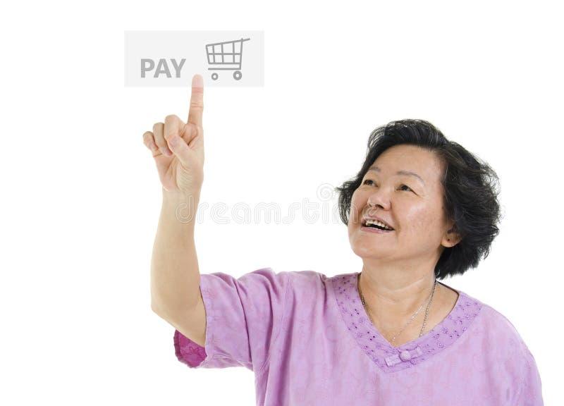Mulher adulta superior que aponta o botão do pagamento fotografia de stock royalty free