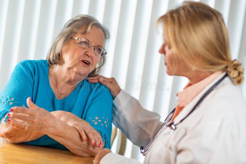 Mulher adulta superior que fala com doutor f?mea About Sore Arm fotografia de stock