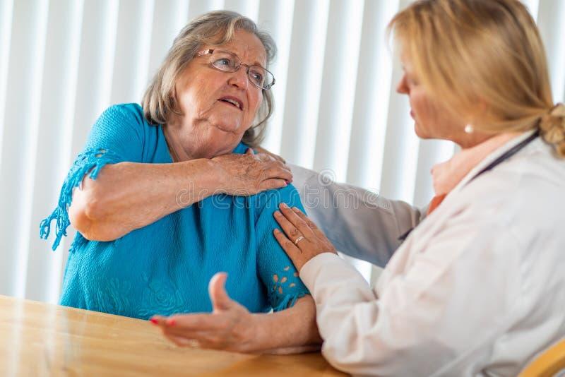 Mulher adulta superior que fala com doutor f?mea About Sore Shoulder imagens de stock royalty free