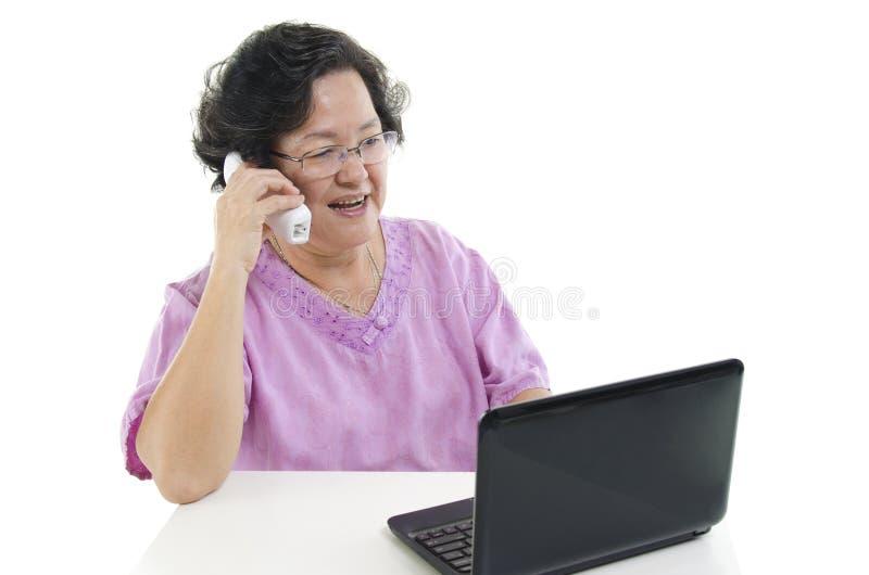 Mulher adulta superior que usa o telefone e o computador fotografia de stock
