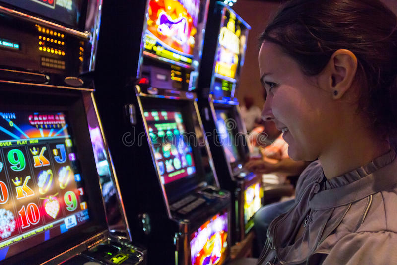 Mulher afortunada que joga slots machines no casino foto de stock royalty free
