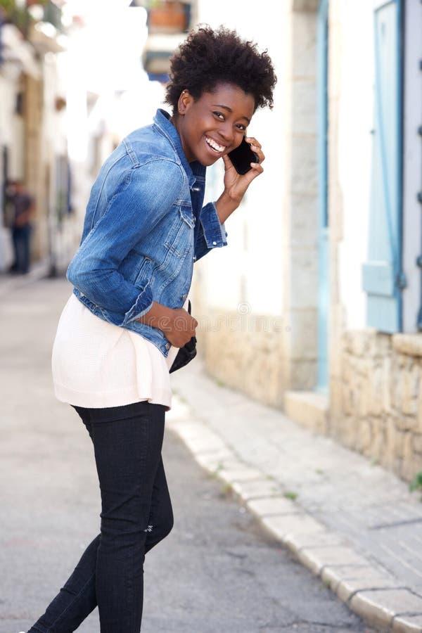 Mulher africana alegre que anda fora com telefone celular imagens de stock