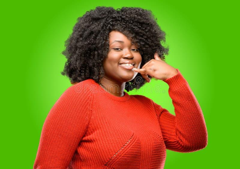 Mulher africana bonita com o cabelo encaracolado isolado sobre o fundo verde imagens de stock