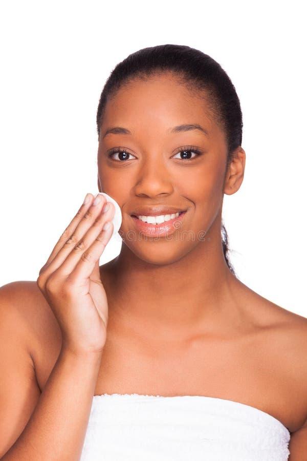 Mulher africana bonita nova que remove a composição - limpeza da pele - imagens de stock royalty free