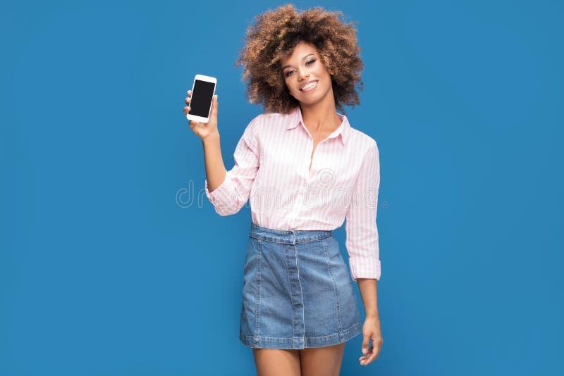 Mulher africana bonita que guarda o telefone celular e o sorriso fotografia de stock